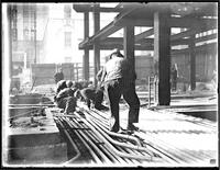 Unidentified workmen doing plumbing or electrical work on a building under construction, New York City (?), undated (ca. 1930-1935).