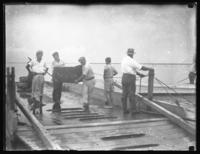 Unidentified boys carrying a trunk off a small ferry, undated (ca. 1930-1935).