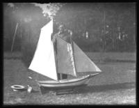 Unidentified man in a yard with a large model sailboat, undated (ca. 1930-1935).