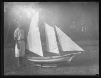 Unidentified boy in a yard with a large model sailboat, undated (ca. 1930-1935).