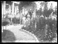 Odessa France Bjorkman, Virginia Bjorkman, and William Bjorkman at the entrance of an unidentified garden, undated (ca. 1930-1935).