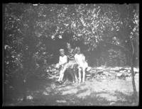 Unidentfied woman with William Bjorkman and Virginia Bjorkman seated on a dry stone wall under trees, undated (ca. 1930-1935).