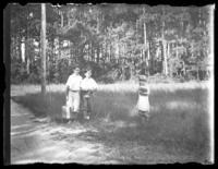 Three unidentified children with schoolbooks, standing in a clearing, undated (ca. 1930-1935).
