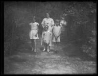 Odessa, Virginia, Peggy, and William Bjorkman standing on a dirt path through trees, undated (ca. 1930-1935).