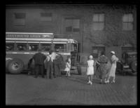 Group gathered around a Greyhound bus, watching a man replace a tire, undated (ca. 1930-1935).