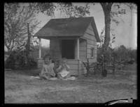 Unidentified toddler and infant seated on the ground in front of a playhouse, undated (ca. 1930-1935).