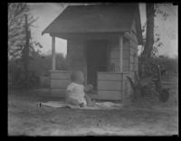 Unidentified infant seated on the ground in front of a playhouse, undated (ca. 1930-1935).