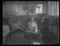 Unidentified infant in a wicker chair, undated (ca. 1930-1935).