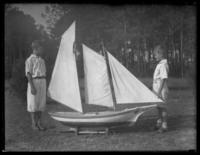 Unidentified boys in a yard with a large model sailboat, undated (ca. 1930-1935).