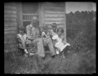Unidentified man sitting on the steps of an old bungalow with the Bjorkman children and another unidentified child, undated (ca. 1930-1935).