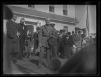 General John J. Pershing standing in front of a house, undated (ca. 1930-1933). Spectators and other officials in the background.