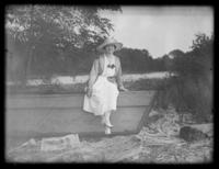 Odessa France Bjorkman sitting on a beached boat, Baltimore, Maryland, undated (ca. 1917-1918).