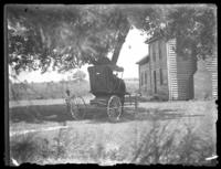 Unidentified little boy sitting on a tree swing, undated (ca. 1930-1935). Horse and carriage beside him.