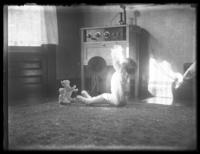 Unidentified child sitting on the floor in footie pajamas, next to an early model radio, undated (ca. 1930-1935).
