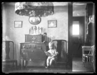 Unidentified toddler sitting in a chair next to an early model radio, undated (ca. 1930-1935).