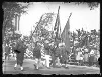 Flag bearing veterans in a military parade along Riverside Drive near the Soldiers' and Sailors' Monument, New York City, undated (ca. 1917-1919).