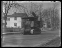 Caterpillar tank driving along a residential road on its way to Washington D.C., undated (ca. 1917-1918).