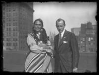 Chief Oskomon and an unidentified man in a suit shaking hands on the roof of a building, Baltimore, Maryland, undated (ca. 1917-1918).