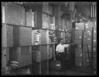 Interior stockroom of unidentified Lord Electric Company store, with unidentified man posing in front of stocked shelves, New York City or Baltimore (?), undated (ca. 1920).