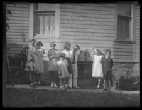 Virginia, Peggy, and William Bjorkman and unidentified children standing outside a house beside a sign that says 'Peter Rabbit Party,' probably Yonkers, N.Y., undated (ca. 1935).