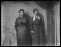 Anna E. Bjorkman and unidentified woman posing near the front door of a house, undated (ca. 1918-1920).