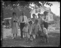 Odessa, Virginia and William Bjorkman in a group portrait with unidentified people and dog under a tree, with a house and a car in the background, undated (1920-1929).