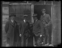 Four unidentified men standing outside an old wooden building, undated (ca. 1920?).