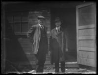 Two unidentified men standing outside an old wooden building, undated (ca. 1920?).