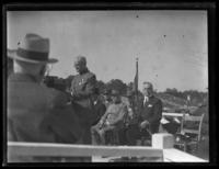 John J. Pershing speaking on an outdoor stage with other officials, including Ferdinand Foch, seated behind, location unidentified, undated (ca. 1919).