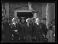 Unidentified WWI officials at the entrance of a building holding flags, flanked by crowds on either side, location unidentified, undated (ca. 1919).