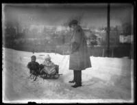 Unidentified man pulling Virginia Bjorkman and an unidentified child on sleds, undated (ca. 1921-1924).