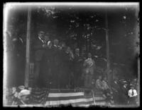 Admiral William S. Benson and unidentified officials standing on a stage with their hats over their hearts, location unidentified, undated (ca. 1917-1921).