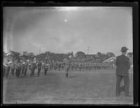 Military band and soldiers standing in formation with spectators in the background, location unidentified, undated (ca. 1930-1935).