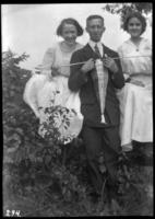 Fritz E. Bjorkman, holding a pennant labelled 'Souvenir 1910,' and two unidentified young women, undated (ca. 1910).