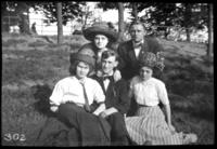 Charles Edward Johnson, an unidentified young man and three unidentified young women seated on a grassy slope, undated (ca. 1910-1913).