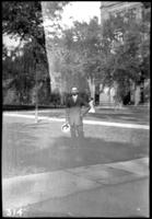 Fritz E. Bjorkman standing in front of unidentified buildings, undated (ca. 1910-1913)