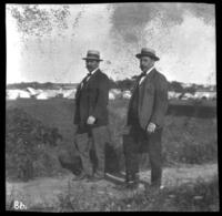Herman Bjorkman and an unidentified man in a path near a large encampment, undated (ca. 1905-1909).
