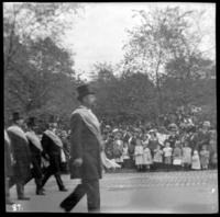 Unidentified officials in sashes walking in a parade, undated (ca. 1905-1909).