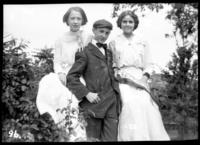 Unidentified young man and  two unidentified young women holding a pennant labelled 'Souvenir 1910,' undated (ca. 1910).
