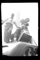 Fritz E. Bjorkman and an unidentified man setting up a motion picture camera on top of a car, Washington, D.C., undated (ca. 1937). Occasion is probably the 1937 Boy Scouts' National Jamboree.