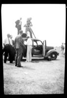 Fritz E. Bjorkman and other unidentified men shooting with a motion picture camera on top of a car, Washington, D.C., undated (ca. 1937). Occasion is probably the 1937 Boy Scouts' National Jamboree.