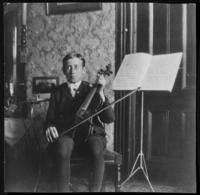 Fritz E. Bjorkman posing with a violin and music, Bronx, N.Y., 1907.