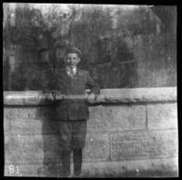 Unidentified boy standing by a wall, undated (ca. 1905-1915)