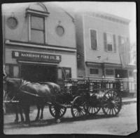 Horse-drawn fire engine parked outside the Harrison Fire Station, New York or New Jersey, undated (ca. 1900-1909).