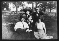 Fritz E. Bjorkman, Charles Edward Johnson, and three unidentified young women seated on a grassy slope, undated (ca. 1910-1913).