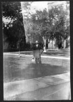 Fritz E. Bjorkman standing in front of unidentified buildings, undated (ca, 1910-1913).