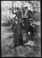 Four unidentified young men posed on some rocks in the woods, undated (ca. 1910-1913).