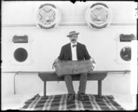 Unidentified member of the Taft party posing on the SS Manchuria with a bundle on his lap, undated [1905].