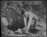 Unidentified man drawing water from Niles' Spring, Bronx, New York City, October 3, 1897.