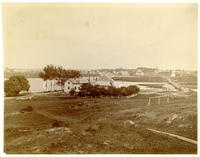 High angle view of unidentified farmstead, with a lake or river and town beyond, undated [c. 1897-1902].